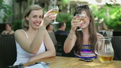 stock-footage-female-friends-raising-a-toast-to-camera-with-white-wine